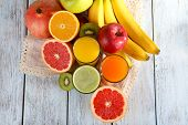 Fruit and vegetable juice and fresh fruits on napkin on wooden background
