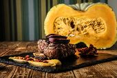 An appetizing steak with a pumpkin in the background