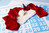 Sanitary pads, white Berber and rose petals on red calendar background