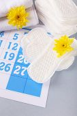 image of menses  - Sanitary pads and yellow flowers on blue calendar background - JPG