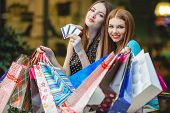 Two girlfriends in shop with shopping bags and credit cards.