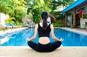 stock photo of padmasana  - Beautiful Asian Girl practicing yoga by the pool lotus pose  - JPG