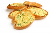 Garlic and herb bread slices on white background.