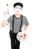 Male mime artist holding a paintbrush and a color pallet isolated on white background