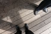 Shoes of two employee standing on Plank