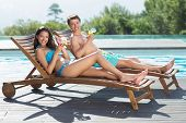 Full length of a young couple sitting on sun loungers by swimming pool