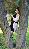 Girl Holding A Green Apple Leaning On A Tree