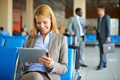 Pretty businesswoman using touchpad while sitting at the airport