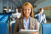 Smiling young woman with touchpad looking at camera while sitting in airport