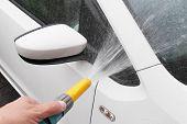 Closeup of man washing car with hosepipe