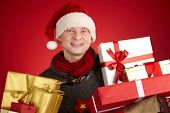 Portrait of happy man in Santa cap holding packed gifts