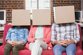 Young casual business team sitting on couch with boxes over heads