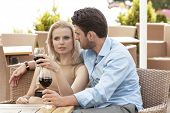 Young couple talking while having red wine at outdoor restaurant