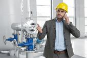Serious young male manager using cell phone in industry