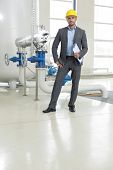 Full length portrait of confident young male manager with clipboard in industry