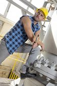 Young manual worker holding wrench in industry