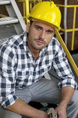 Portrait of young male worker in hard hat sitting on steps at industry