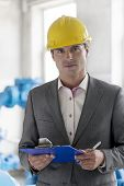 Portrait of young male supervisor holding clipboard in industry