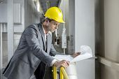 Young male architect reading blueprint while leaning on railing in industry
