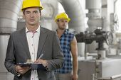 Portrait of young male supervisor writing on clipboard with manual worker in background at industry