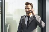 Young businessman using cell phone outside office building