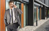 Portrait of businessman using cell phone outside office