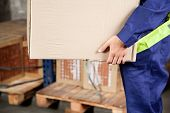 Midsection of young foreman in uniform carrying cardboard box at warehouse