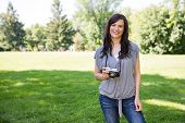 Portrait of beautiful young woman with digital camera in park