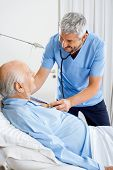 Smiling male caretaker checking senior man's chest with stethoscope in bedroom at nursing home
