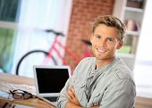 Portrait of student sitting in front of laptop