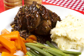 stock photo of lamb shanks  - Cooked lamb shanks with gravy and vegetables - JPG