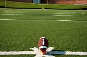 image of football field  - American football on tee on field with goal post in background - JPG