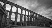 stock photo of aqueduct  - The ancient Roman aqueduct in black and white - JPG