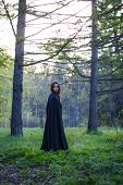 stock photo of cloak  - the girl with the black cloak in the forest - JPG