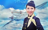 pic of air hostess  - Portrait of beautiful smiling stewardess on a background of an airplane flying in the sky - JPG
