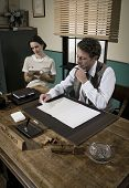image of 1950s style  - Director and secretary working together at desk 1950s style office - JPG