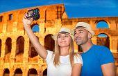 Постер, плакат: Beautiful couple taking picture of them self on Coliseum background happy young family spending sum