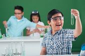 stock photo of reagent  - Happy excited boy looking at the test tube with chemical reagent - JPG