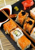 picture of soy sauce  - Arrangement of Various Maki Sushi with Smoked Salmon Eel and Tempura Crab on Stone Plate with Ginger Soy Sauce and Wasabi closeup on Straw Mat background - JPG