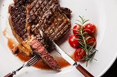 stock photo of ribeye steak  - Sliced medium rare grilled Beef steak Ribeye with grilled cherry tomatoes on white plate background - JPG