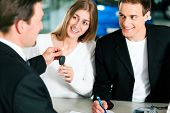 Sales situation in a car dealership, the young couple is signing the sales contract and gets the key