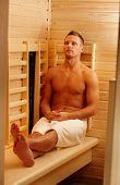 Постер, плакат: Спортивный человек наслаждаясь сауной в полотенце сидя с закрытыми глазами