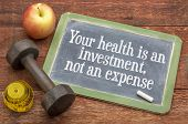 Your health is an investment, not an expense - wellness concept -  slate blackboard sign against wea poster