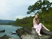 Photos of a beautiful woman in a pink dress on a rocky seashore