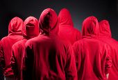 backs of people in red clothes against dark background