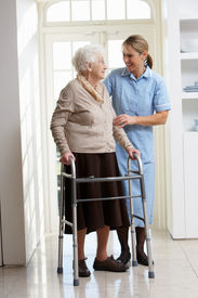 stock photo of zimmer frame  - Carer Helping Elderly Senior Woman Using Walking Frame - JPG
