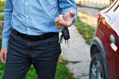 Man Gives Car Keys Outdoors With Red Car On Background. poster