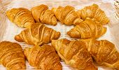 Selective Focus On The Front Small Croissant. Small Croissants, Homemade Cakes. Blurred Background.  poster