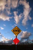 an End sign sits at the end of a road against a Blue Sky with Amazing fluffy clouds poster
