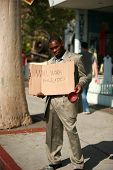 a thursty african american male model stands on a city street with a cardboard sign that reads